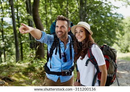 Happy couple hiking together in mountains - stock photo
