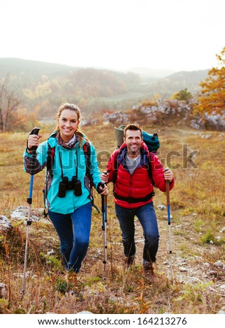 Happy couple hiking with backpacks and sticks in mountains - stock photo