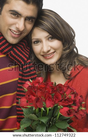 Happy couple holding a bouquet of roses - stock photo