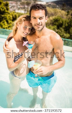 Happy couple holding cocktails in the pool and looking at the camera - stock photo