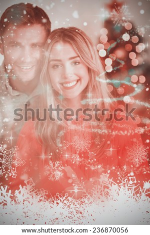Happy couple holding each other against glittering christmas tree design - stock photo