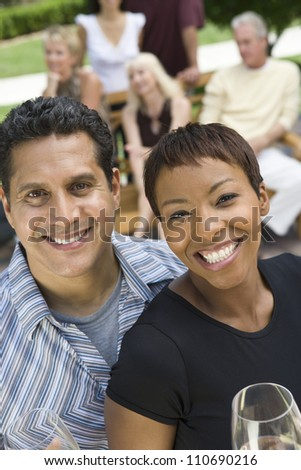 Happy couple holding glasses of wine with friends - stock photo