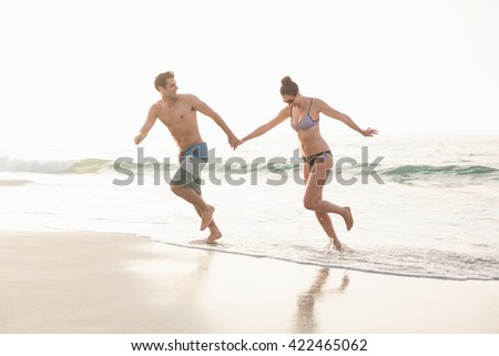 Happy couple holding hands and running on the beach - stock photo