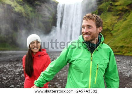 Happy couple holding hands by waterfall outdoors in front of Skogafoss on Iceland. Couple visiting famous tourist attractions and landmarks in Icelandic nature landscape on Golden Circle. - stock photo