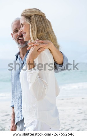 Happy couple holding hands on the beach - stock photo