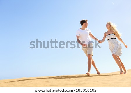 Happy couple holding hands running having fun in playful and romantic relationship under sun and blue sky in desert. Two young lovers cheerful together on romance in summer. Joyful man and woman. - stock photo