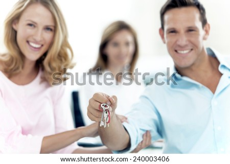 Happy couple holding keys with financial adviser on background - stock photo