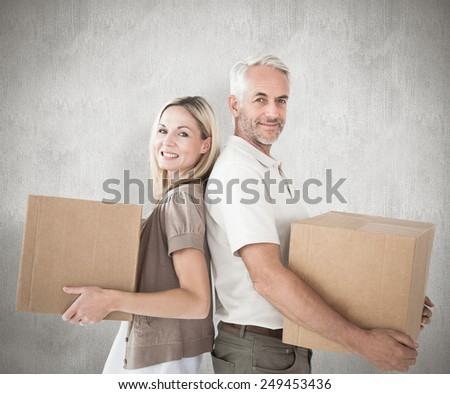Happy couple holding moving boxes against weathered surface - stock photo