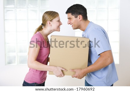 Happy couple holding one cardboard box. They're looking at each other. Side view.