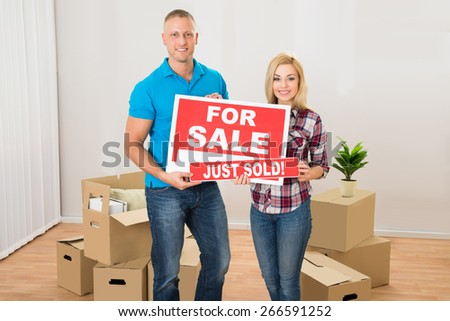 Happy Couple Holding Sold Sign In Their New Home - stock photo