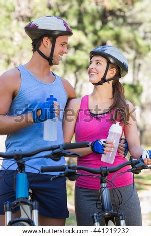 Happy couple holding water bottles while riding bicycle at forest - stock photo