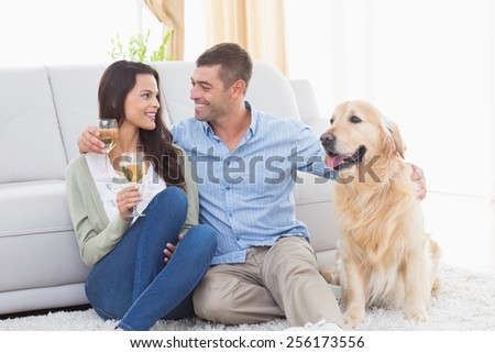Happy couple holding wine glasses while sitting with dog at home - stock photo