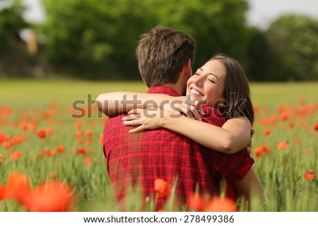 Happy couple hugging affectionate after proposal in a green field with red flowers - stock photo