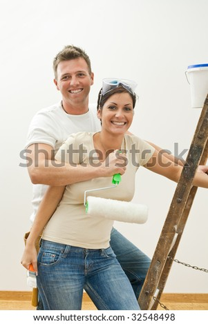 Happy couple hugging and smiling, while improving their new home. - stock photo