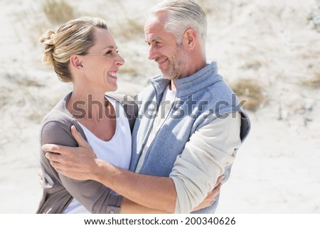 Happy couple hugging on the beach looking at each other on a bright but cool day - stock photo