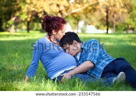 Happy couple - Husband and his pregnant wife relaxing in autumn park