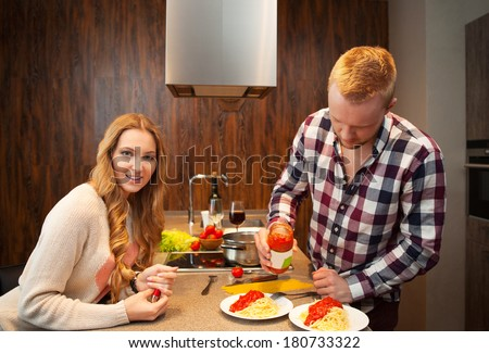Happy couple in a kitchen cooking pasta and drinking red wine - stock photo