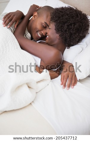 Happy couple in bed together at home in the bedroom - stock photo