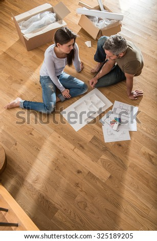 Happy couple casual clothes sitting barefoot stock photo royalty happy couple in casual clothes sitting barefoot on the wooden floor of their new house malvernweather Choice Image