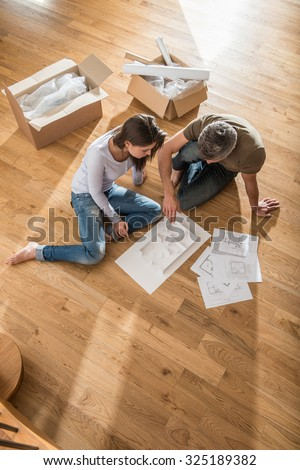 Happy couple in casual clothes sitting barefoot on the wooden floor of their new house. They are looking at the house model, blueprints and plans They are surrounded by open cardboard boxes - stock photo