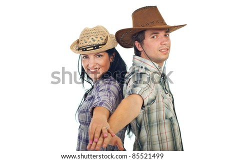 Happy couple in cowboy's hats standing back to back and holding their hands in front of camera isolated on white background