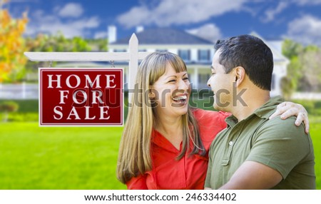 Happy Couple in Front of For Sale Real Estate Sign and New House. - stock photo