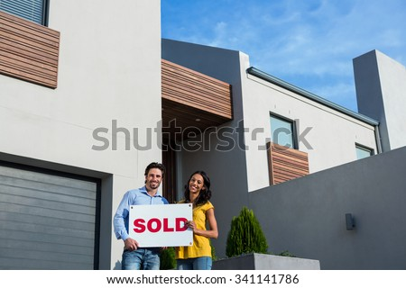Happy couple in front of new house with sold sign - stock photo