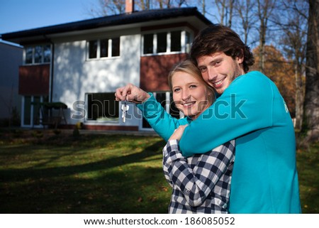 Happy couple in front of the new house  - stock photo