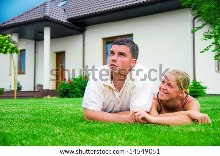 Happy couple in front of their ideal house - stock photo