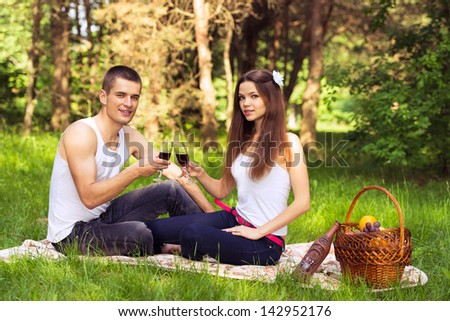 happy couple in love at picnic and drinking wine - stock photo