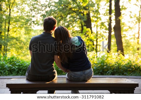 Happy couple in love at yellow and green summer park - stock photo