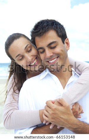 happy couple in love daydreaming together on the beach