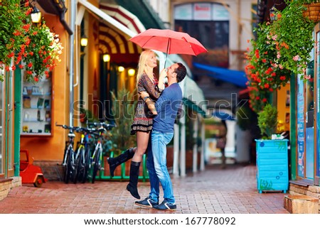 happy couple in love embracing on colorful street - stock photo