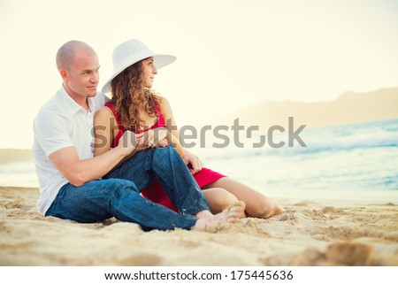 Happy couple in love enjoying sunset at the beach
