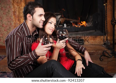 Happy couple in love enjoying wine near fireplace - stock photo