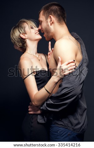 Happy couple in love in a moment before kiss over black background.