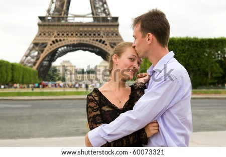 Happy couple in love in Paris near the Eiffel Tower - stock photo