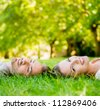 Happy couple in love laying on the floor outdoors - stock photo