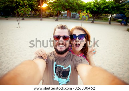 Happy couple in love on beach summer vacations.Joyful laughing girl piggybacking on young Caucasian boyfriend playing and having fun in sunny tropical destination for travel holiday.Make funny selfie - stock photo