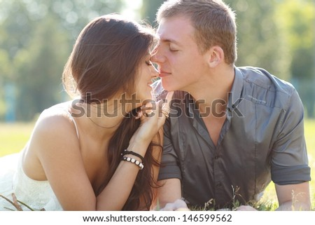 Happy Couple in Love. Park. Young Couple Lying on Grass Outdoor. Soft summer colors - stock photo