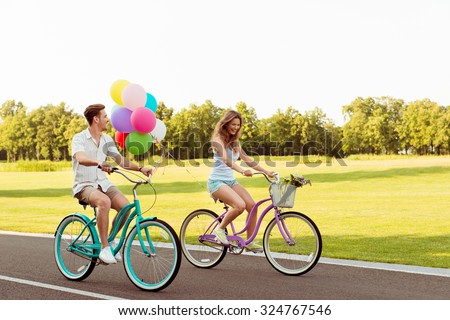 happy couple in love riding bicycles having fun - stock photo