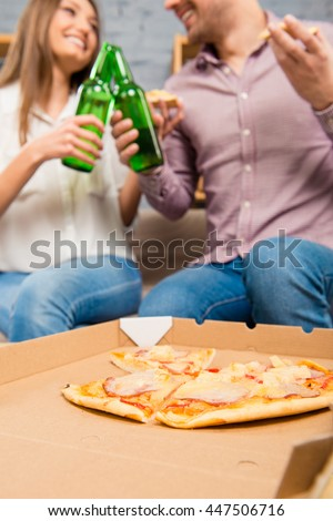Happy couple in love spending holiday with pizza and beer - stock photo