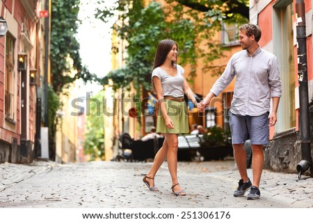Happy couple in love walking in Gamla Stan, Stockholm city visiting Sweden. Young adults tourists on travel or Swedish urban people in summer walking on a date. - stock photo