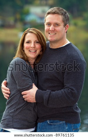Happy couple in love with each other.  They are standing in front of a beautiful, scenic lake setting.
