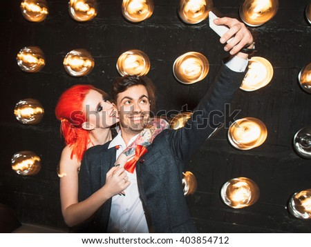 Happy couple in nightclub do selfie on mobile phone. Young redheaded girl with big tattoo hugs young laughing men. Party selfie of boyfriend and girlfriend on black background. - stock photo