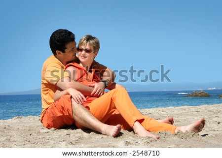 Happy couple in orange clothes on the beach - stock photo