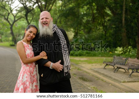 Happy couple in park older bearded Caucasian man with young Asian woman