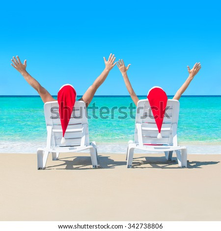 Happy couple in red Santa hats relaxing at romantic tropical beach with palms on sun beds - Christmas or New Year's vacation in hot countries concept - stock photo