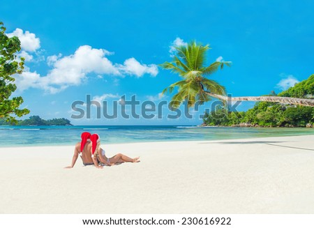 Happy couple in santa hats at tropical sandy palm beach, christmas and new years vacation concept, Seychelles, Mahe island, Baie Lazare