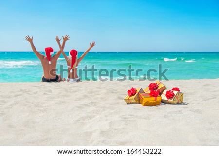 happy couple in santa hats hands up at sea beach with christmas packed  golden gifts - stock photo